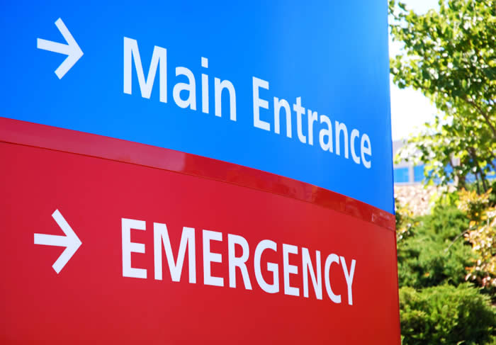 Hospital sign with arrows pointing towards the main entrance and emergency room