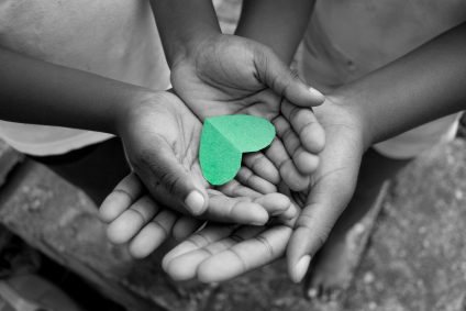 A child's hands, holding a green paper heart, resting in a parent's hands