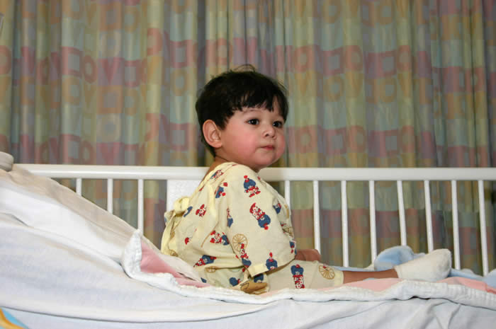 Young child sitting in crib