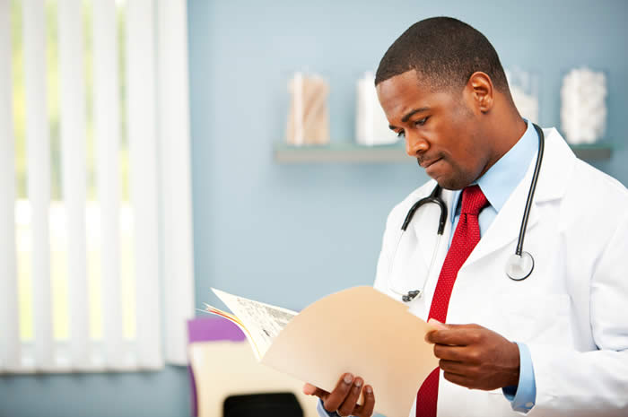 A doctor examines records in a file folder