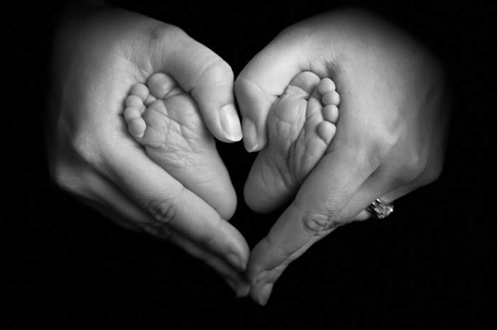 Two hands in the shape of a heart holding a child's feet