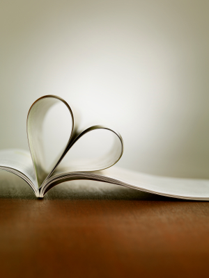 An open book with the pages folded into a heart shape